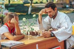 Schackmatch mellan vuxna människan och barnet royaltyfri foto