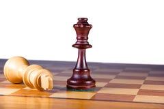 Schackmatt vit konung som framme ligger av den vita drottningen Arkivfoto