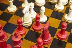 Schackstycken i röd och vit färg över tabellen Royaltyfri Foto