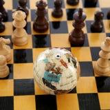 Schackstycken och jordklot Royaltyfri Bild