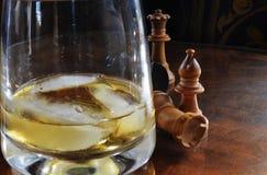 Schackstycken och whiskyexponeringsglas Royaltyfri Bild