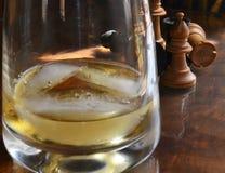 Schackstycken och whiskyexponeringsglas Royaltyfri Foto