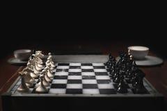 Schackstycken på schackbrädet Mörk bakgrund och rök royaltyfri foto
