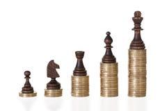Schackstycken på staplade mynt Arkivbild