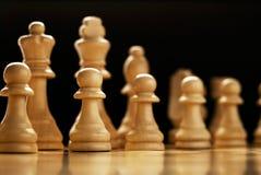 Schackstycken uppställda på ett schackbräde arkivfoton