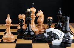 Schackstyckena och högen av kontrollörer som förläggas på schackbrädet Royaltyfri Foto