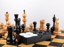 Schackstyckena och uppsättningen av kontrollörer som förläggas på schackbrädet Fotografering för Bildbyråer