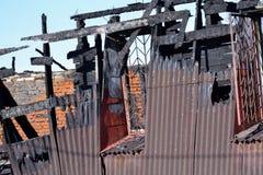 Schade aan het dak van de brand Baksteenhuis, door brand wordt beschadigd die mens die brandblusapparaat controleert stock foto's