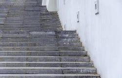 Schade en vuile treden in de stad met wit huismuur stock foto's