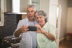 Schadelijk hoger paar die selfie in keuken nemen stock foto's