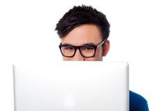 Schadelijke jongen die zijn gezicht met laptop verbergen Stock Fotografie