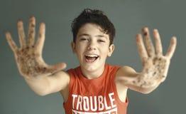 Schadelijke tienerjongen met vuile handglimlach stock foto