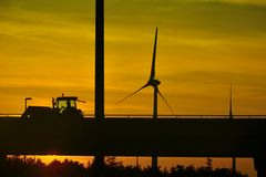 Schaduw van een voorbijgaande tractor en een windmolen bij een fantastische zonsondergang Stock Afbeeldingen