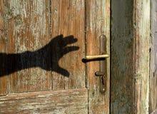 Schaduw van hand en oude deur Stock Fotografie