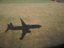 Schaduw van het vliegtuig op de gebieden tijdens het landen stock foto
