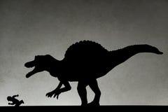 Schaduw van spinosaurus die mens op muur achtervolgen royalty-vrije stock afbeeldingen