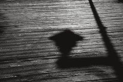 Schaduw van straatlantaarn op een houten promenade stock fotografie