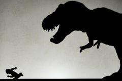 Schaduw van tyrannosaurus die mens op muur achtervolgen Stock Afbeeldingen
