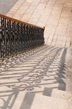 Schaduwen van decoratieve gegoten metaalbalusters op steenstappen royalty-vrije stock fotografie