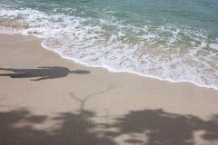 Schaduwen van mensen en boom op het strand Stock Foto's