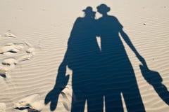 Schaduwen van paar toeristen op zand Royalty-vrije Stock Foto