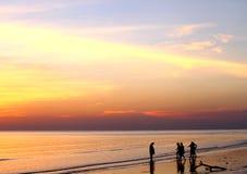 Schaduwmensen bij zonsondergang langs de kust Stock Afbeelding