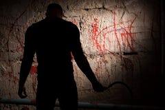 Schaduwrijk cijfer dichtbij bloedvlekke muur stock fotografie