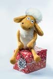 Schafe mit einem Weihnachtsgeschenk lokalisiert auf weißem Hintergrund Lizenzfreies Stockbild