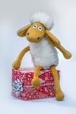 Schafe mit einem Weihnachtsgeschenk lokalisiert auf weißem Hintergrund Lizenzfreie Stockfotografie