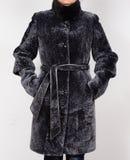 Schaffellpelzmantel lokalisiert auf grauem Hintergrund Pelzmantel auf Modell ohne Gesicht Stockbilder