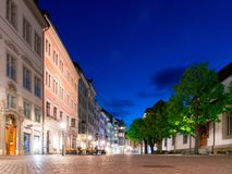 Schaffhausen, SH / Switzerland - 22 April, 2019: the Kirchhofplatz square on a spring evening with people eating out and bright. City light colors under a blue royalty free stock photography