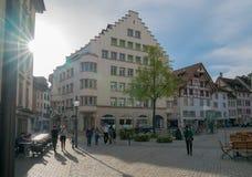 Schaffhausen, SH  / Switzerland - 22 April 2019: tourists enjoying a sightseeing walk through the historic old town of. Schaffhausen in Switzerland on a warm stock images