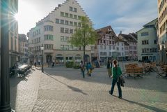 Schaffhausen, SH  / Switzerland - 22 April 2019: tourists enjoying a sightseeing walk through the historic old town of. Schaffhausen in Switzerland on a warm royalty free stock image
