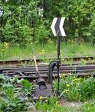 Schakel de spoorwegsporen van de oude spoorlijn die met gras wordt overwoekerd stock foto