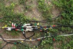 Schakelaars voor muziek en microfoon voor een feestelijke partij Draden met schakelaars xlr leugen ter plaatse en op het gras stock foto