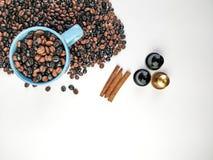 Schale blauer Kaffee, wenn die Kaffeebohnen umgeben und drei Zimtstangen und drei Kaffeekapseln, mit weißem Hintergrund oberseite stockfotografie