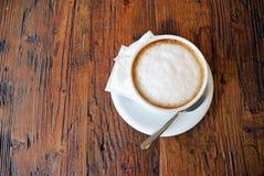 Schale Cappuccino auf dem Holztischhintergrund Stockfotografie