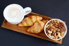 Schale Cappuccino, croissantsand Schüssel von Nüssen Lizenzfreie Stockbilder