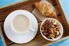 Schale Cappuccino, croissantsand Schüssel von Nüssen Stockbilder
