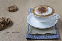 Schale Cappuccino mit Kakao auf Holztisch Stockbilder