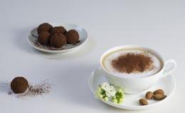 Schale Cappuccino mit Schokoladenpralinen Stockfotografie