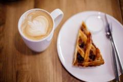 Schale Cappuccino mit Torte lizenzfreies stockbild