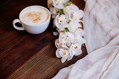 Schale Cappuccino und Blumen lizenzfreie stockfotografie