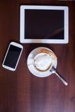 Schale Cappuccino- und Handy- und Tabletten-PC auf Holztisch Lizenzfreie Stockfotografie