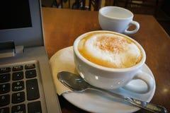 Schale Cappuccino und Laptop auf Holztisch stockfotografie