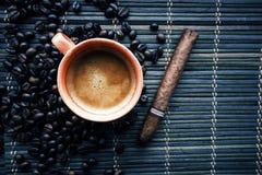 Schale coffe mit Kaffeebohnen und Zigarre lizenzfreie stockbilder