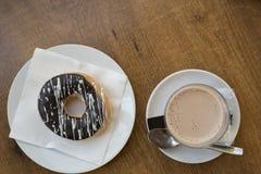 Schale der heißen Schokolade mit einem Donut bedeckt mit Schokolade auf einen Holztisch Lizenzfreie Stockfotos