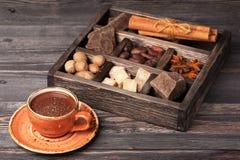 Schale der heißen Schokolade und der Weinleseholzkiste mit Gewürzen und dunkler Schokolade lizenzfreie stockbilder