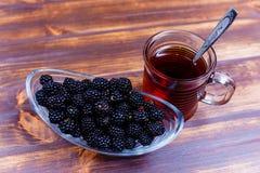 Schale der Nahaufnahme des schwarzen Tees und der Brombeeren lizenzfreie stockbilder