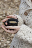 Schale des Bechers des heißen Getränks in den weiblichen Händen auf warmer Strickjacke Lizenzfreie Stockfotografie